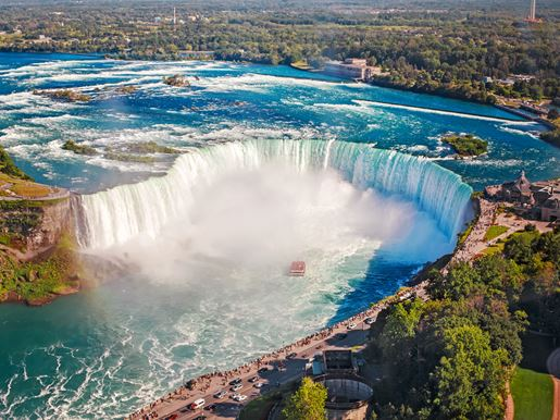 Canva Aerial Top Landscape View Of Niagara Falls And Tour Boat In Water Between US And Canada. Horseshoe Of Famous Canadian Waterfall On Sunny Day
